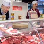 butcher preparing meat behind counter