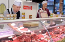 butcher preparing meat behind counter