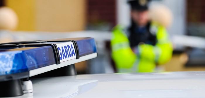 Garda Siochana Irish police officer behind a car
