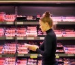 Woman purchasing a packet of meat at the supermarket
